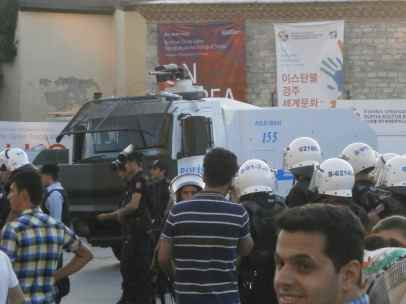 Police with gas masks alongside armoured vehicle with eater canon.